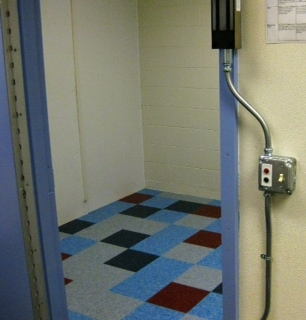 Photo looking into the open door of a school seclusion room.